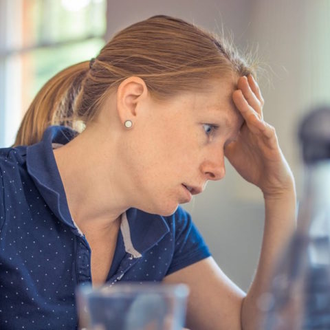 Woman with her hand on her head looking stressed