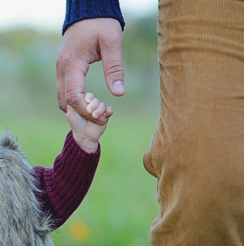 Father holding young daughters hand